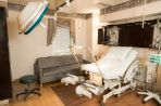 Medical equipment is kept out of sight using custom cabinetry and ceiling storage.